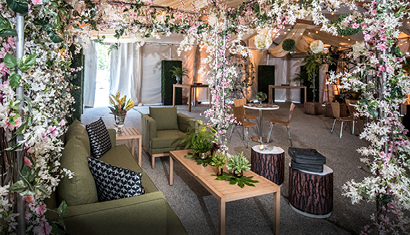 tented event with floral and green furniture