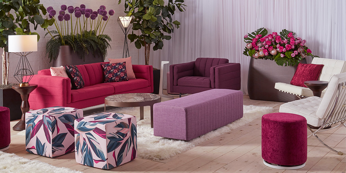 Lounge area with sofa, chair and ottomans in various berry color tones.
