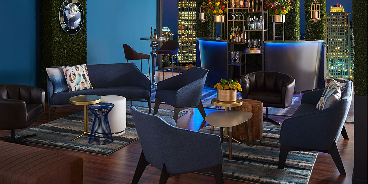 Cocktail reception with blue furniture and a lighted bar