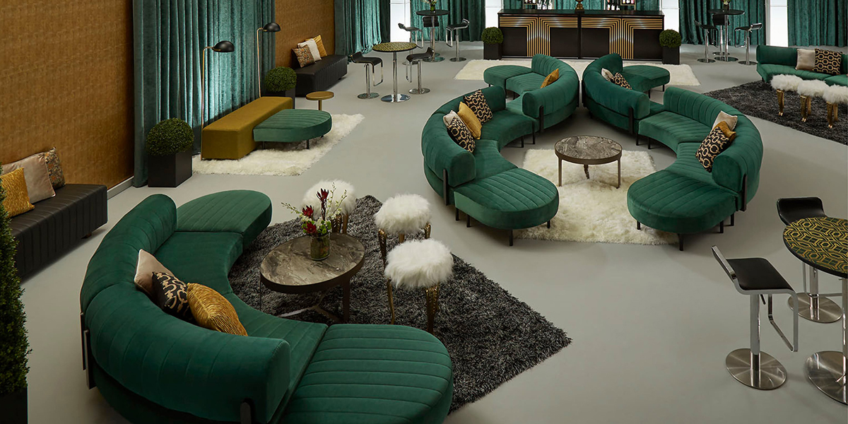 Gala event with large green soft seating sectionals and cream and black accents.